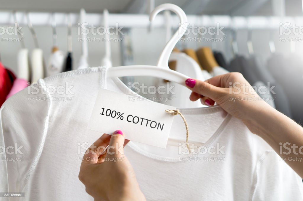 T-shirt made of 100% and hundred percent cotton. Customer looking at the material, fabric and textile of a fashion product in clothes store or shop. Woman holding label and price tag with text. stock photo