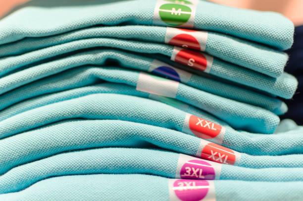 T-shirts em uma prateleira em uma boutique - foto de acervo