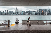 Senior Chinese woman sits and admire the Hong Kong skyline from Tsim Sha Tsui, Kowloon, while an older man walks behind her.