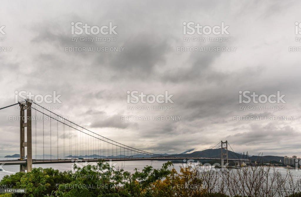 Morning under dark rainy sky. Tsing Ma Bridge crossing gray Ma Wan...