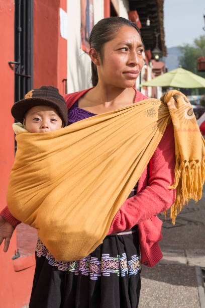 Tsotsil woman carrying baby in shawl stock photo