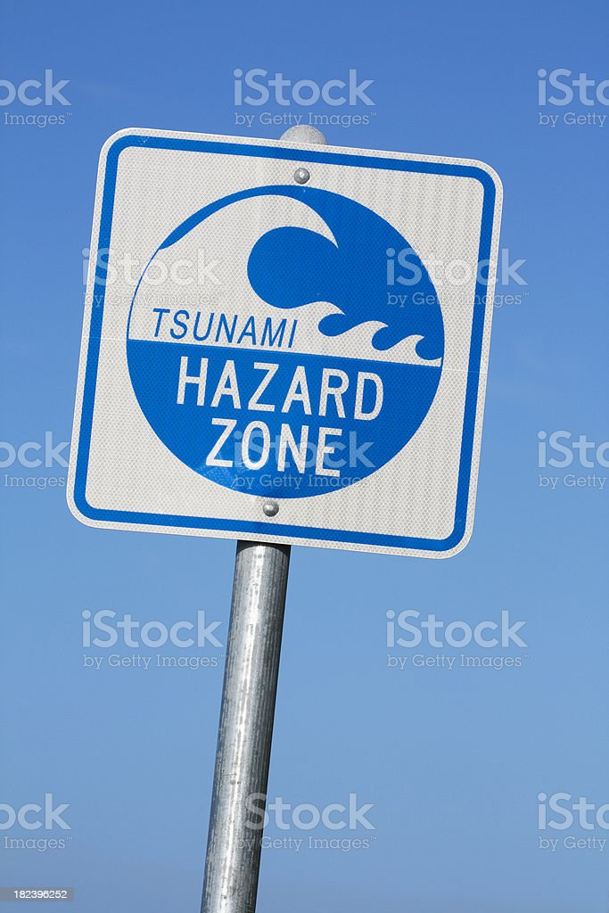 Tsunami hazard zone warning sign against blue sky stock photo