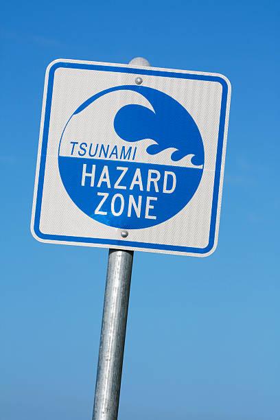 Tsunami hazard zone warning sign against blue sky stock photo