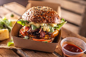 Tasty homemade burger takeaway in a box of recycled paper on wooden boards.