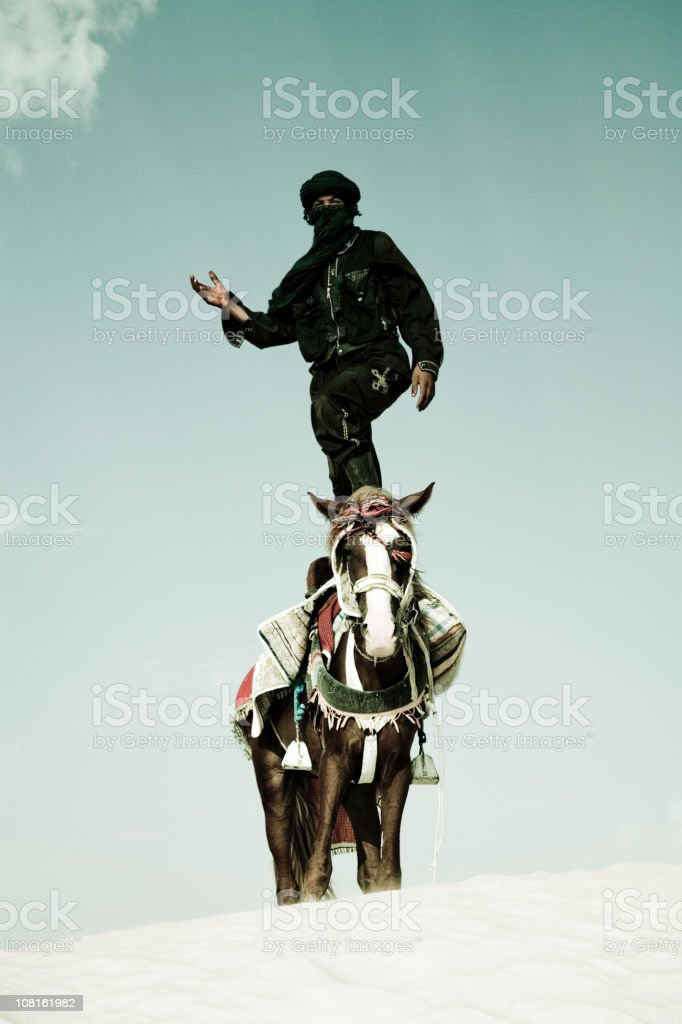 Tuareg Standing on Horse in Sand Dune stock photo