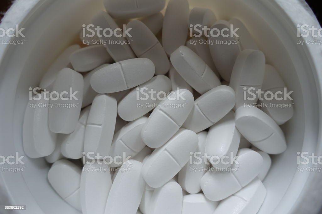 Tub filled with white tablets from above stock photo