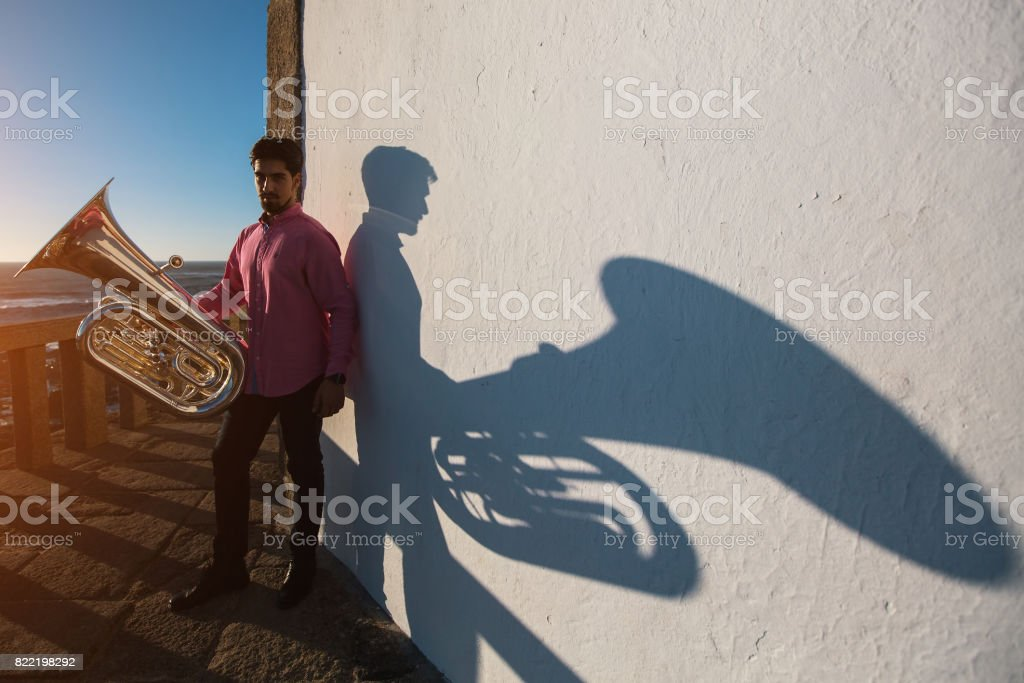 Tuba - instrument. Young man standing with trumpet in hand, a big shadow on a white wall. stock photo