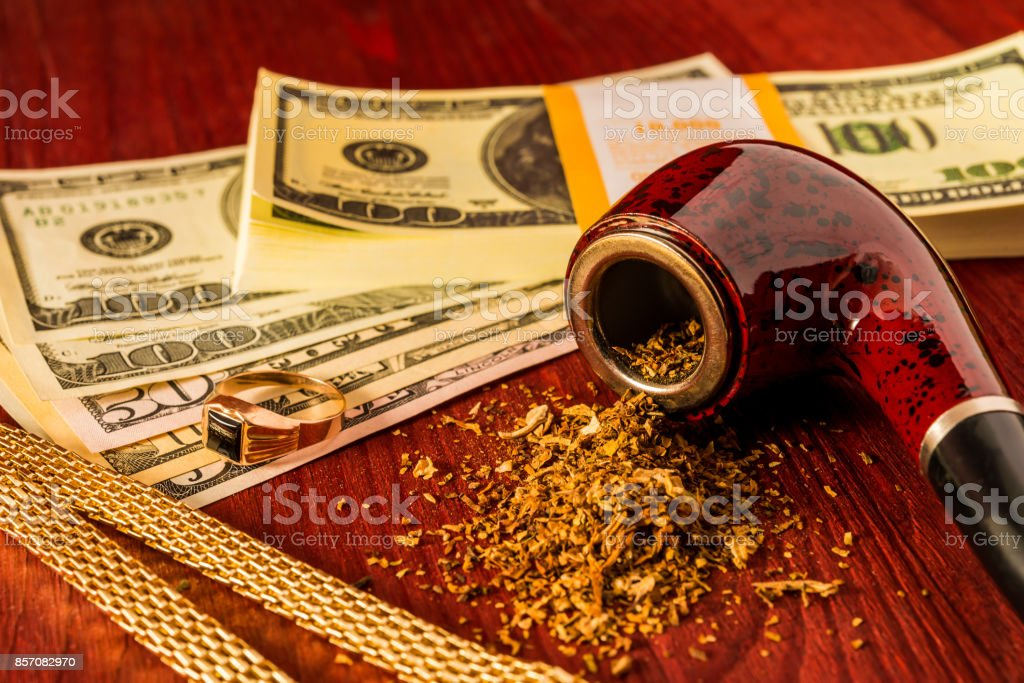 Tube for smoking tobacco and money with golden chain and ring on a wooden table stock photo