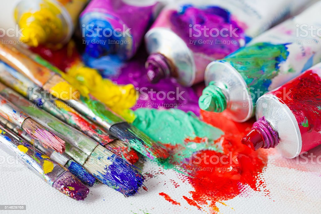 Tubes of multicolor oil paint and artist paintbrushes on canvas stock photo