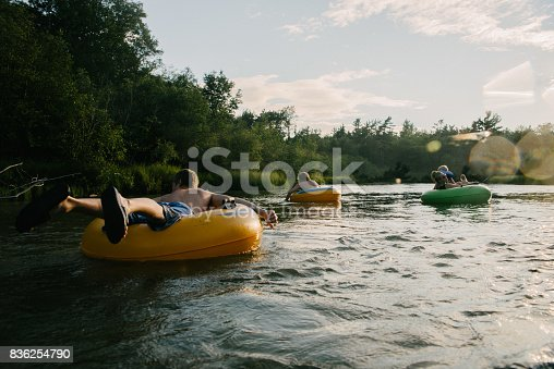 Young people floating down river in inner tubes