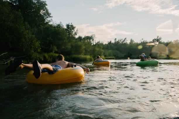 Tubing in river Young people floating down river in inner tubes tube stock pictures, royalty-free photos & images