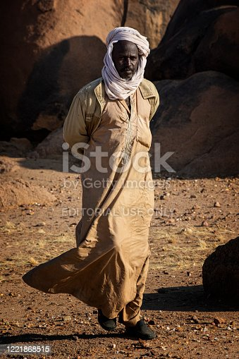 Kalait, Chad - February 06,2020: A mid aged man  of the Tubu people close to a waterhole in the Sahara desert of the Ennedi region in  North-East Chad. The small oasis with water are essential for the Tubu people and their large camel herds. The Ennedi massif was declared as an UNESCO World Heritage site in 2016.