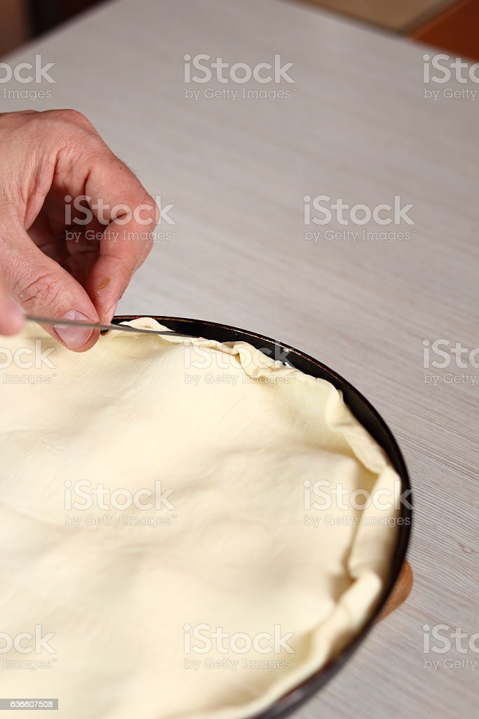 Tuck in edges of puff pastry with knife stock photo
