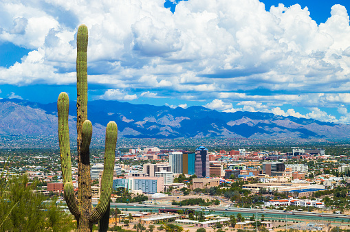 Aerial view of Downtown Tucson and the Tucson area with a Saguaro Cactus in the foreground and dramatic clouds and the Santa Catalina Mountains in the background, during summertime (including during the summer monsoon.)