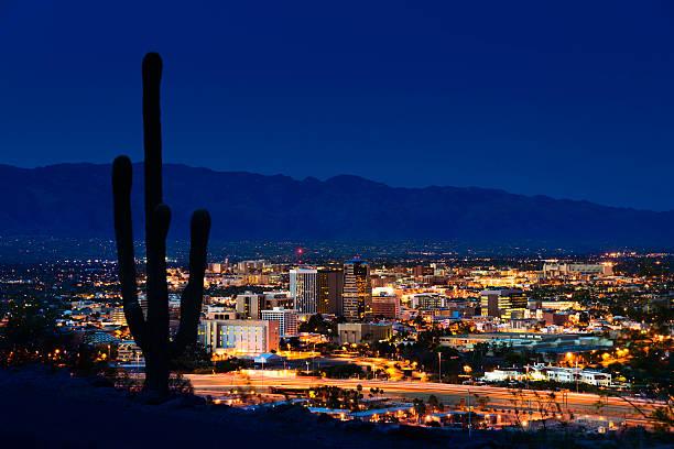 Tucson Arizona at night framed by saguaro cactus and mountains stock photo