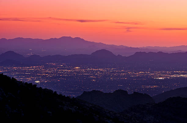Tucson at Night Tucson's city lights at dusk with the mountains in the foreground and in the distance. tucson stock pictures, royalty-free photos & images