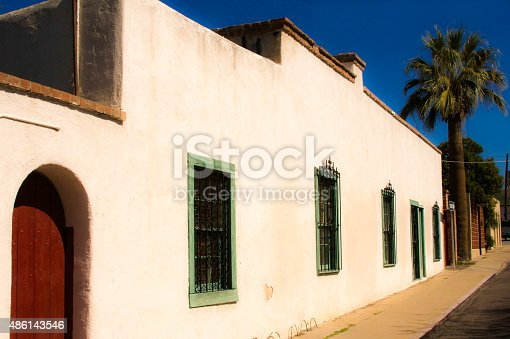 A street scene with a sunlit traditional white building, sidewalk, and palm tree in Tucson, AZ. Brilliant blue sky.
