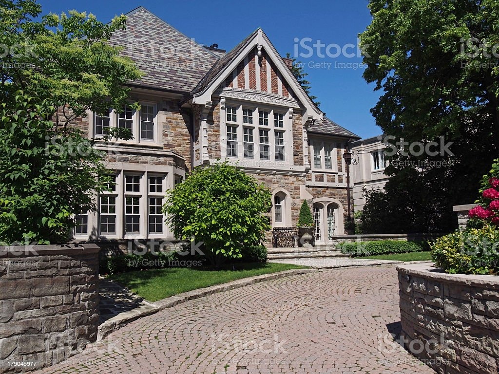 Tudor Style House With Stone Driveway And Greenery Stock Photo
