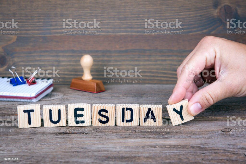 Tuesday. Wooden letters on the office desk, informative and communication background stock photo