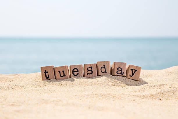 Tuesday word on sea beach stock photo