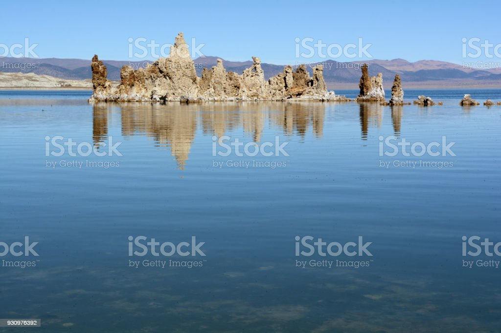 A tufa formation reflects in the calm water of Mono Lake on a sunny afternoon stock photo