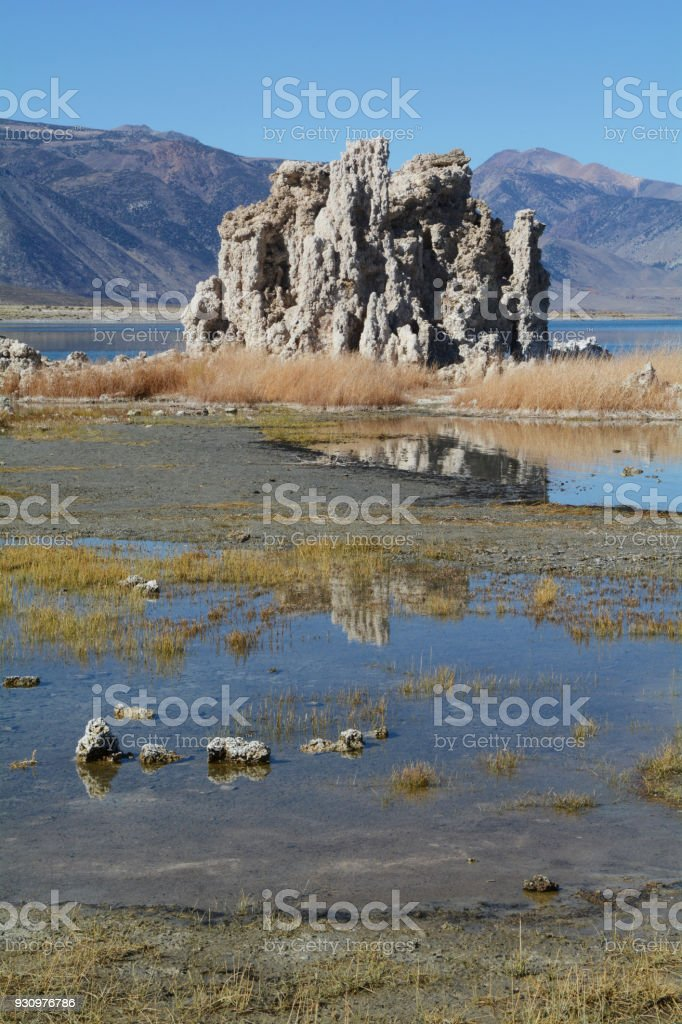 A tufa reflects in the water along the beach at Mono Lake in northern California stock photo