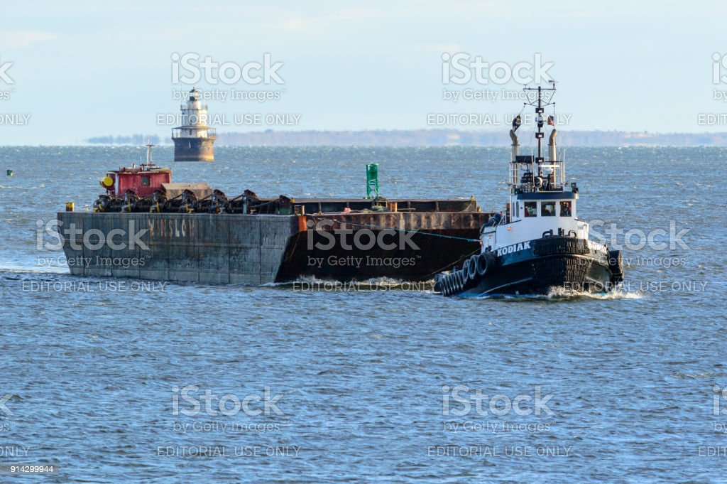 Tug and barge passing Butler's Flat lighthouse stock photo
