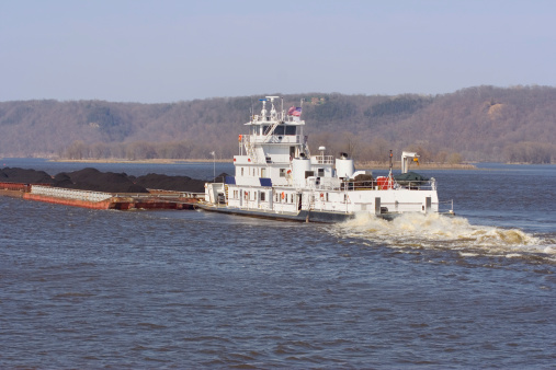 Tug boat on the mississippi with a barge of coal