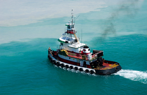 Tug boat heading to assist a boat in caribbean waters, leaving wake in back of it on a diagonal moving right lower side into left.