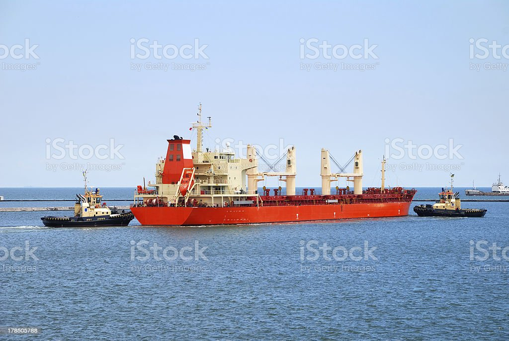 Tug boat helps to maneuver the ship royalty-free stock photo