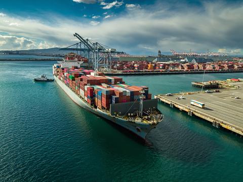 Tug Boat Maneuvering Cargo Ship at Dockside in Port of Long Beach