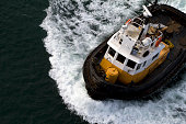 Tug boat cruising over water, aerial.