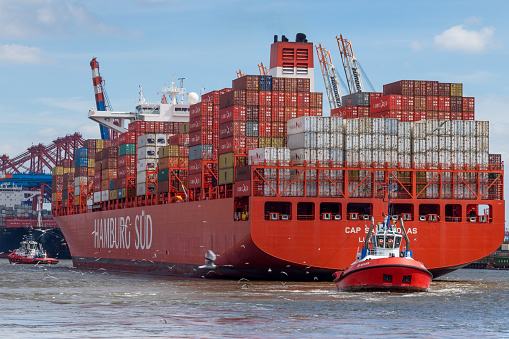 Tug boat pulls large container ship
