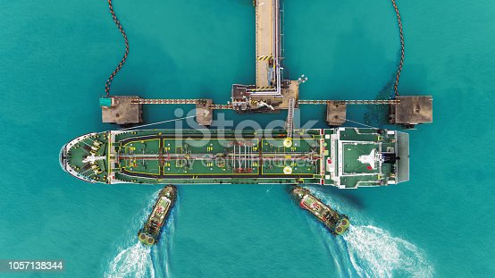 637816284istockphoto Tug boats drag Oil ship tanker park to port for transfer crude oil to oil refinery. 1057138344