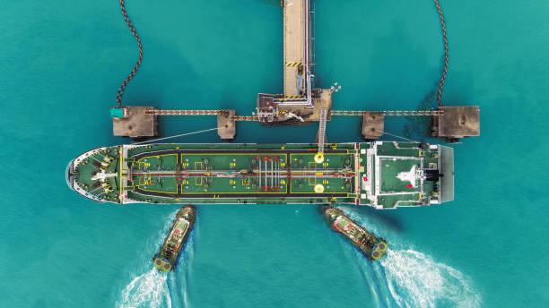 sleepboot boten slepen olie schip tanker park aan poort voor overdracht ruwe olie naar olieraffinaderij. - industrieel schip stockfoto's en -beelden