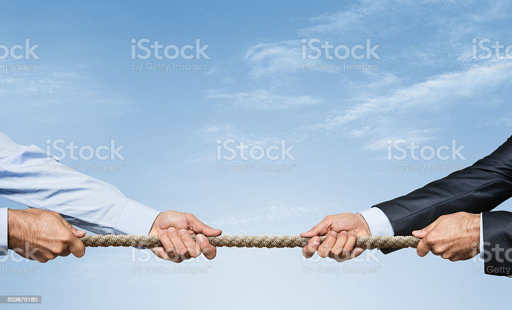Tug of war Two businessman pulling a rope in opposite directions over sky background with copy space Adult Stock Photo