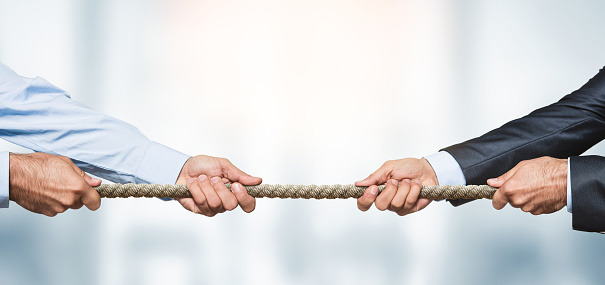 Tug of war, two businessman pulling a rope in opposite directions over defocused background with copy space