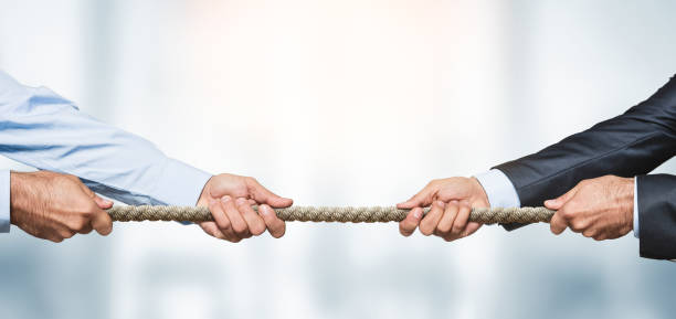 Tug of war, two businessman pulling a rope in opposite directions Tug of war, two businessman pulling a rope in opposite directions over defocused background with copy space business stock pictures, royalty-free photos & images