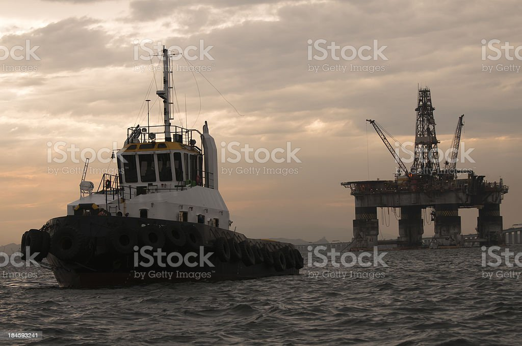 Tugboat and an oil platform stock photo