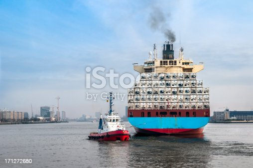 Rear view of a large cargo vessel, being manoeuvred by a tugboat in the port of Rotterdam, The Netherlands.