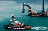 A Tugboat and a dredging barge work the harbor in the Caribbean.