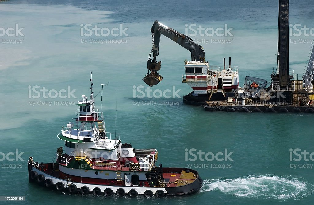 Tugboat and Dredge Dredging the Harbor stock photo