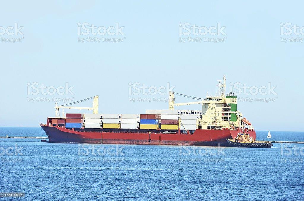 Tugboat assisting cargo ship royalty-free stock photo