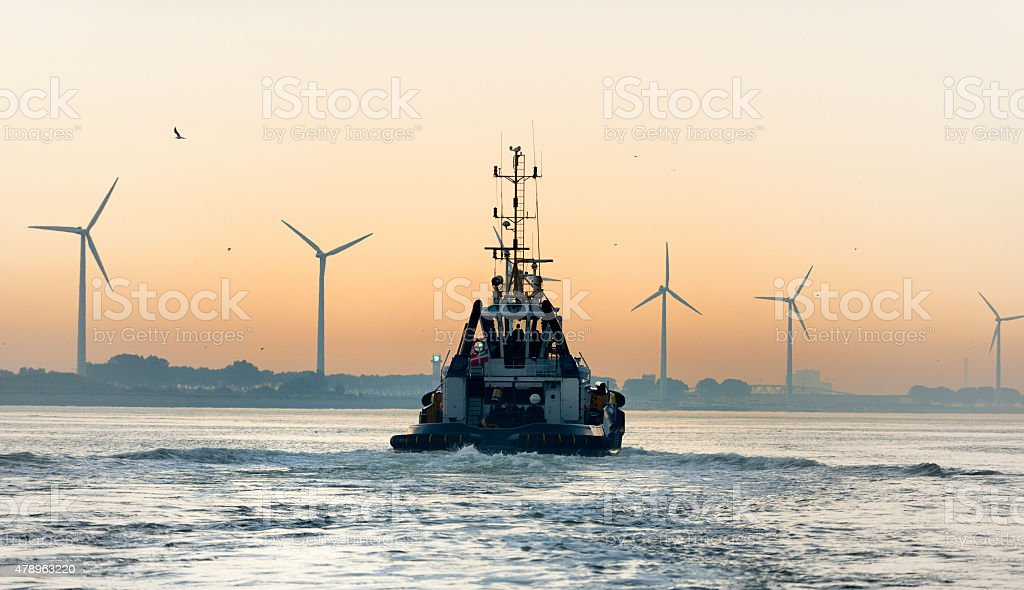 Rear view on a tugboat sailing at full speed in harbor at sunrise,...