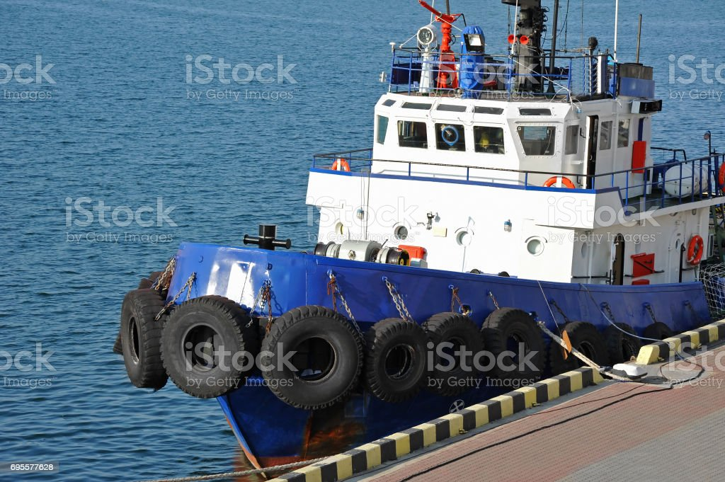 Tugboat in harbor quayside stock photo