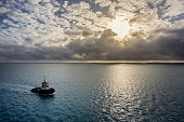A solitary tugboat in a vast ocean under a beautiful cloudscape