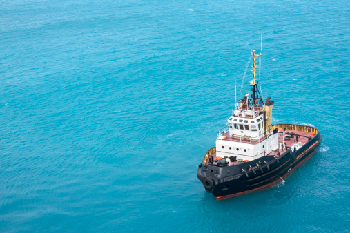 Single tugboat floats in aqua blue ocean water.