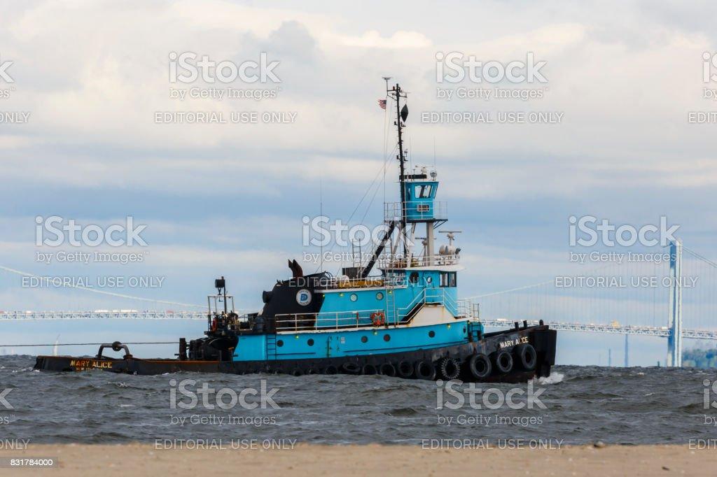 Tugboat Mary Alice On Choppy Jamaica Bay Waters, Verrazano Narrows Bidge In Background stock photo