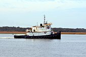 Tugboat cruising along the river background
