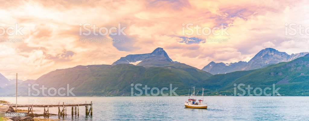 Tugboat or fishing boat at sunset in Norway, Europe. Ship in...